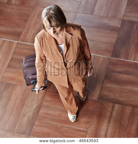 Elderly woman with rolling suitcase in a hotel