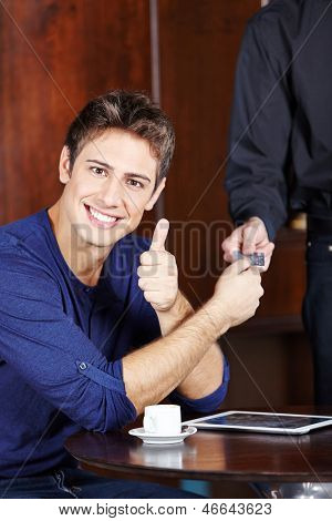 Young man paying with credit card in caf���© and holding his thumb up