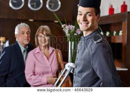 Smiling concierge with senior couple in a hotel