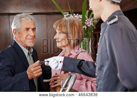 Senior people taking key card from concierge in a hotel