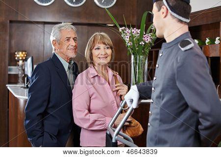 Senior couple at check-in at hotel looking at concierge