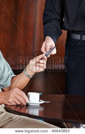 Man paying coffee in caf���© with his credit card