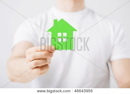 closeup picture of man hand holding green house