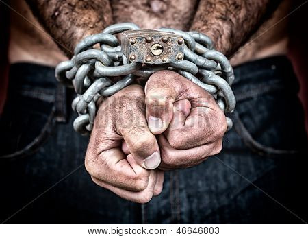 Dramatic detail of the chained hands of an adult man (with a strong chain and padlock)