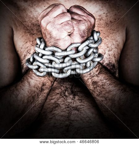 Dramatic detail of the chained hands of an adult shirtless man (with a strong chain and padlock)
