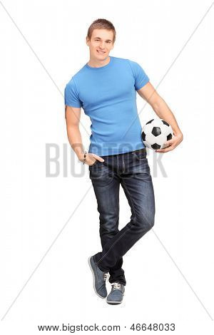 Full length portrait of a young man leaning on a wall and holding a soccer ball isolated on white background