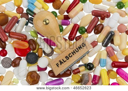stamp on colorful tablets, symbolic photo for drug counterfeiting and piracy