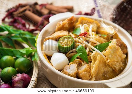 Hot and spicy Malaysia Curry Noodle or laksa  mee with hot steam in clay pot, decoration setup, serve with chopsticks. Malaysian cuisine.