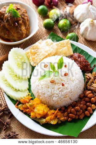 Nasi lemak traditional malaysian spicy rice dish, fresh cooked with hot steam. Served with belacan, ikan bilis, acar, peanuts and cucumber. Decoration setup.