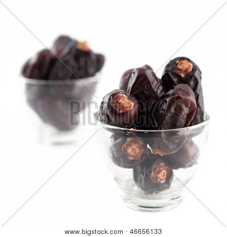 Dates fruit. Pile of dried date fruits in glass isolated on white background.