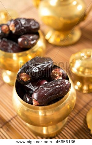 Dates fruit. Pile of fresh dried date fruits in golden metal bowl.