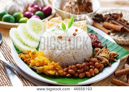 Nasi lemak traditional malaysian hot and spicy rice dish, fresh cooked with hot steam. Served with belacan, ikan bilis, acar, peanuts and cucumber. Decoration setup.