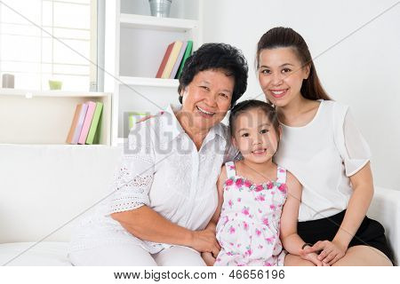 Family generations. Happy Asian family at home, grandparent, parent and grandchild sitting on sofa smiling looking at camera.