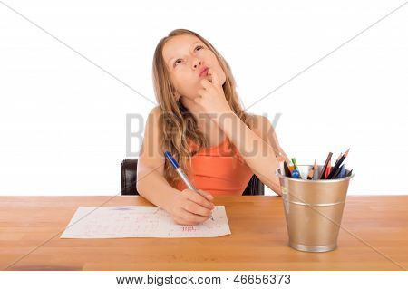 Child Sitting At A Table Trying To Make A Drawing