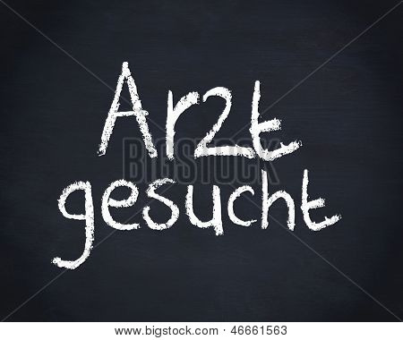 German word arzt gesucht written on a blackboard with a chalk, means