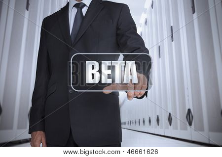 Businessman in a data center selecting label with beta written on it