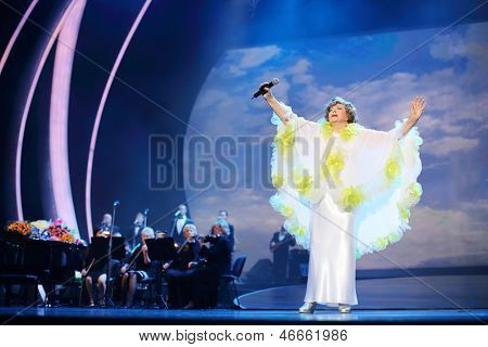 MOSCOW - OCTOBER 14: Edyta Piecha in white rises hands at her anniversary concert in Kremlin Palace, on October 14, 2012 in Moscow, Russia. Famous Russian singer Edita Piecha sings on stage 55 years.