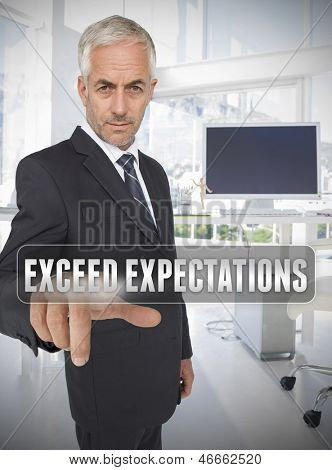 Businessman touching the term exceed expectations in his office