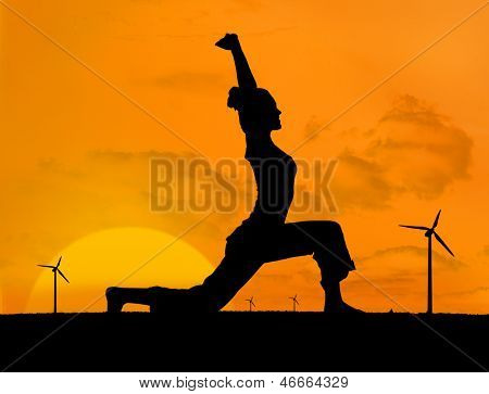 Silhouette of woman doing yoga with wind turbines on the background under sunset