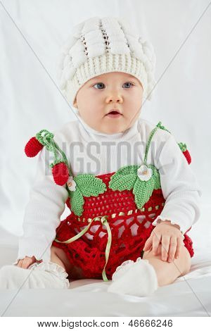 Portrait of little girl dressed in strawberry suit sitting on white coverlet