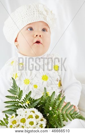 Portrait of little girl with open mouth in white clothes, who sits on white coverlet with bunch of flowers
