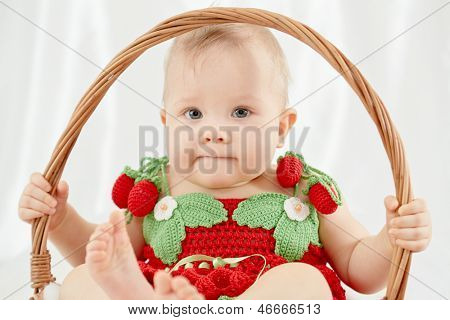 Portrait of little girl dressed in knitted strawberry suit sitting in wicker basket and holding on to basket handle
