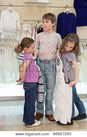 The boy helps girls to choose clothes in shop of childrens clothing, focus on boy
