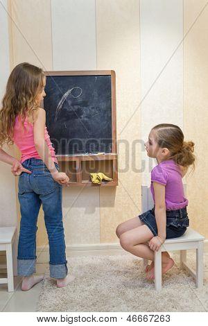 Zwei Mädchen im Spielzimmer auf die Tafel zeichnen