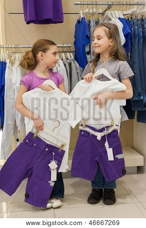 Two smiling girls trying on the same dress in the store children clothes
