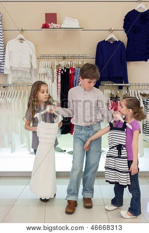 The boy helps girls to choose dress in shop of children clothing
