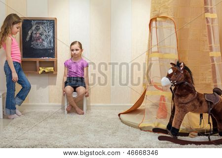 Two little girls playing in the game-room and draw