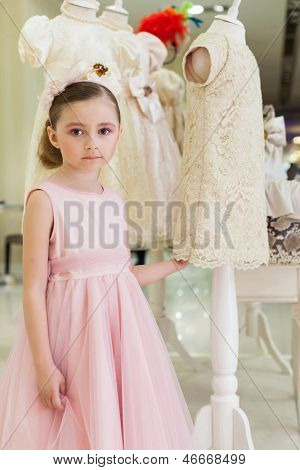 Beautiful girl in a pink dress in a modern store children clothes