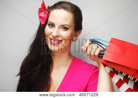Portrait of young happy smiling woman with shopping bags,  over gray background
