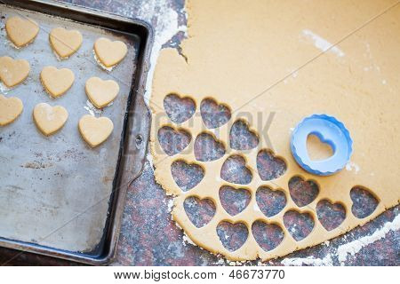 Plastic Heart Shaped Cookie Cutter And Raw Dough Cookies On Metal Baking Tray