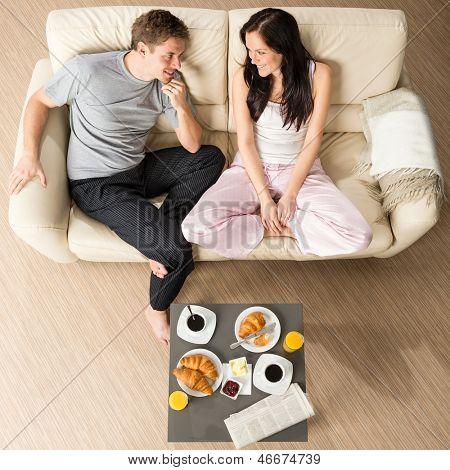 Joyful couple sitting in the morning before breakfast