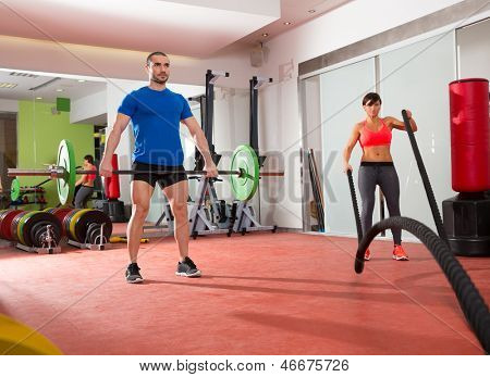 Crossfit fitness gym weight lifting bar man and woman battling ropes workout