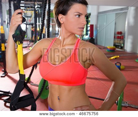 Crossfit fitness woman standing at gym holding trx posing