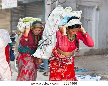 KATHMANDU, NEPAL - MAY 19: Nepalese women carry things in the traditional way on May 19, 2013 in Kathmandu, Nepal.