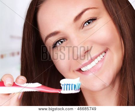 Closeup portrait of beautiful female clean teeth in bathroom, health lifestyle, dental care, teeth whitening, freshness concept