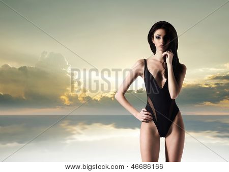 Young, sexy and beautiful woman in swimsuit over the sunset background