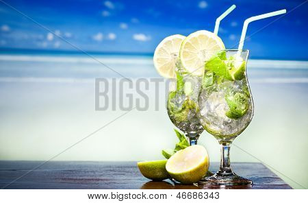 Mojito cocktail with lime and mint against sea background