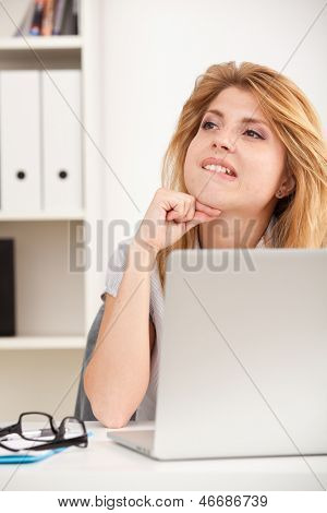 Portrait of beautiful young business woman sitting at desk in the office