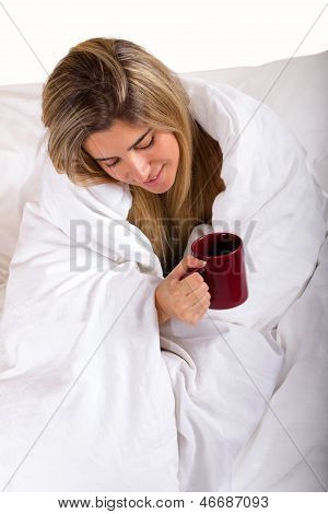 Young Woman Under White  Blanket Holding A Mug