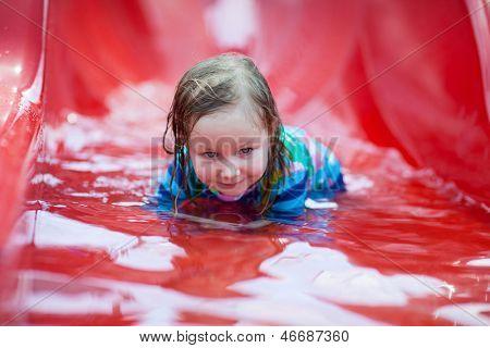 Portrait of little girl on water slide at aquapark