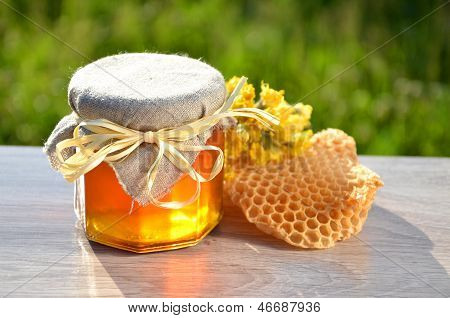 jar full of delicious fresh honey piece of honeycomb and wild flowers in apiary