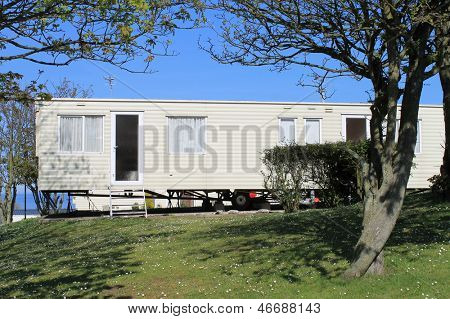 Scenic view of static caravan on trailer park under trees.