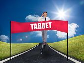 Young smiling businessman running on a road in the middle of green area with a banner with target wr