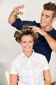 stock photo of hairspray  - Portrait of female customer with hairstylist setting curls with hairspray in salon - JPG