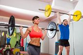 stock photo of gymnastic  - Crossfit fitness gym weight lifting bar by woman and man group workout - JPG