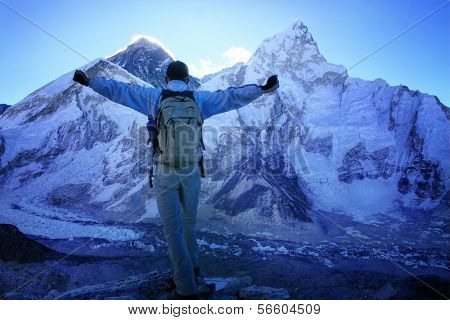 Man facing Mount Everest (8848m) and Nuptse Mountain (7861m) just before sunrise, standing on the Kala Patthar summit, Himalayas, Nepal